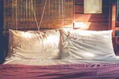 关闭两白色在床上的被弄皱的枕头与从床屋子的右手放热的阳光早晨时间的在乡下 免版税图库摄影