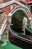 关闭两艘长平底船的铁船首和古色古香的桥梁在威尼斯 免版税库存照片
