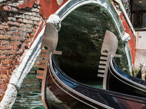 关闭两艘长平底船` s铁船首和古色古香的桥梁在威尼斯 库存照片