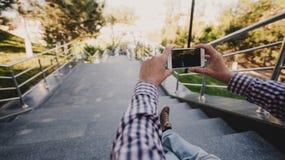 关闭为与他巧妙的电话的一个人好的看法照相,当坐台阶时 免版税库存照片
