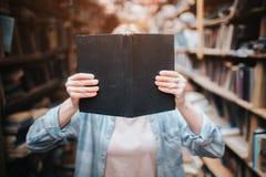 关闭举行书和闭合值的一个白肤金发的女孩她的与它的面孔 在大中的少妇立场在架子中 免版税库存照片