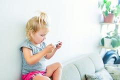 关闭举行和使用与在白色墙壁背景的巧妙的电话的美丽的矮小的女婴 孩子和技术骗局 免版税库存照片