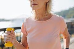 关闭举行黄色哑铃的年长女性 免版税库存照片