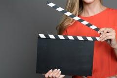 关闭举行clapperboard的一名白肤金发的妇女 免版税库存照片