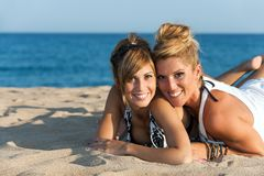 关闭二个女朋友纵向海滩的。 免版税库存图片