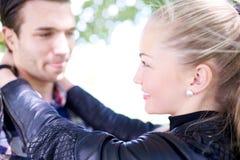 关闭互相微笑甜年轻的恋人 免版税库存照片