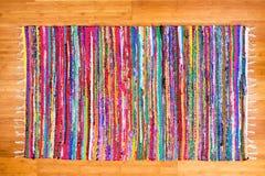 关闭五颜六色的手在竹地板上的被编织的地毯 免版税图库摄影