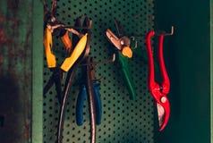 关闭五颜六色的worktools剪刀,修枝剪,垂悬在绿色墙壁上的钳子在棚子 堆有启发性照片  库存照片