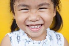 关闭亚洲与happi的孩子暴牙的微笑的面部面孔的面孔 库存图片