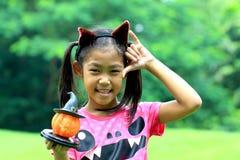 关闭亚洲女孩举行南瓜玩偶画象  库存图片