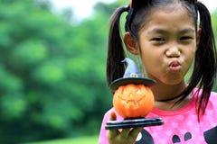关闭亚洲女孩举行南瓜玩偶画象  库存照片