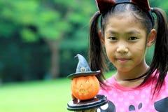 关闭亚洲女孩举行南瓜玩偶画象  免版税库存图片
