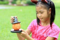 关闭亚洲女孩举行南瓜玩偶画象  免版税库存照片