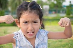 关闭亚洲小女孩的画象有一个恼怒的表示的 库存照片