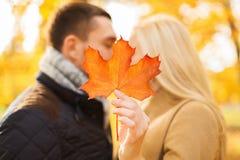 关闭亲吻在秋天公园的夫妇 免版税库存照片