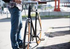 关闭人和固定的齿轮自行车在城市街道上 免版税库存图片