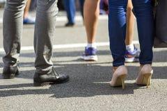 关闭人和妇女腿用不同的鞋子,快速地走沿混凝土路的高跟鞋在明亮的晴天 繁忙的lifes 库存图片