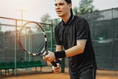 关闭人在两只手中的拿着网球拍调直罢工 免版税库存图片