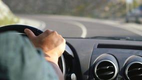 关闭人在驾驶在漫长的路的方向盘的` s手一辆汽车沿山 库存照片