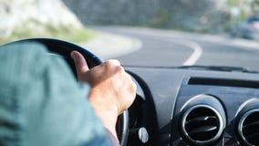 关闭人在驾驶在漫长的路的方向盘的` s手一辆汽车沿山 图库摄影