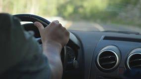 关闭人在驾驶在漫长的路的方向盘的` s手一辆汽车沿山 免版税库存照片