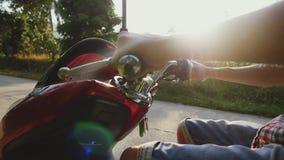 关闭人在驾驶在热带晴朗的路的摩托车旅客的轮子的` s手摩托车通过太阳 影视素材