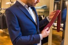 关闭人尝试的领带在服装店 免版税图库摄影