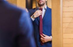关闭人尝试的领带在镜子 免版税库存图片