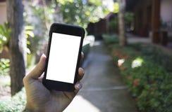 关闭人拿着智能手机的手,巧妙的电话弄脏了在手段,在屏幕上的孤立白色中的方式视图 库存图片