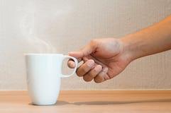 关闭人的手停滞一杯白色咖啡 免版税库存照片