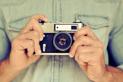 关闭人的手画象拿着葡萄酒照相机的 免版税库存图片