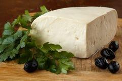关闭从母牛` s牛奶在一个土气木切板,装饰的wi的传统保加利亚新鲜的未成熟的酸奶干酪 库存照片