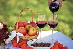 关闭从瓶倾吐的红葡萄酒到玻璃,在自然,苹果,巧克力糖篮子的野餐  免版税库存图片