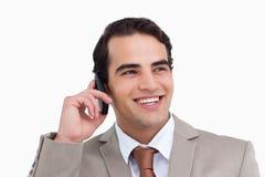 关闭他的移动电话的微笑的销售人员 免版税库存照片