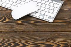 关闭企业工作场所的看法有无线键盘、钥匙和老鼠的在老黑暗的木桌背景 免版税库存图片