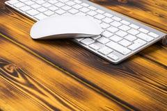关闭企业工作场所的看法有无线键盘、钥匙和老鼠的在老黑暗被烧的木桌背景 免版税库存图片