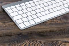 关闭企业工作场所的看法有无线键盘的,在老黑暗的自然木桌背景的钥匙 免版税图库摄影