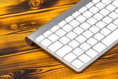 关闭企业工作场所的看法有无线键盘的,在老黑暗被烧的木桌背景的钥匙 库存照片