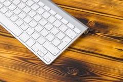 关闭企业工作场所的看法有无线键盘的,在老黑暗被烧的木桌背景的钥匙 免版税库存照片