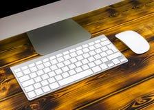 关闭企业工作场所的看法有计算机、无线键盘、钥匙和老鼠的在老黑暗被烧的木桌上 库存图片