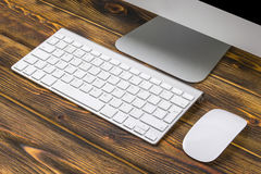 关闭企业工作场所的看法有计算机、无线键盘键和老鼠的在老黑暗被烧的木桌背景 免版税库存图片