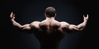 关闭体育man& x27; 被隔绝的s肌肉后面 库存图片