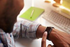 关闭佩带巧妙的手表的商人在设计事务所 免版税库存照片