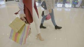 关闭佩带脚跟的年轻时尚上瘾者女孩前进在购物中心做周末购物- 股票录像