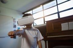 关闭佩带虚拟现实模拟器的男孩打手势,当站立反对钢琴时 免版税图库摄影