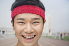 关闭佩带头饰带的微笑的运动员画象 免版税库存照片