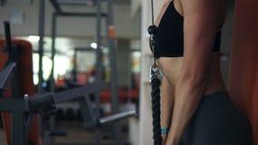 关闭使做与重量的黑体育胸罩的适合的妇女震惊英尺长度锻炼通过以前推挤绳索,手 股票视频