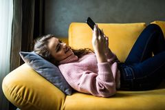 关闭使用一个巧妙的电话的一个轻松的女孩在家说谎在沙发在客厅 免版税图库摄影