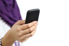关闭使用一个巧妙的电话的阿拉伯妇女的手 免版税库存图片