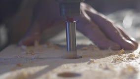 关闭使用一个电手钻的木工作者通过托架操练孔 影视素材
